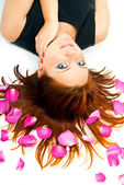 Girl lying on a background of rose petals — Stock Photo