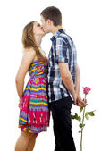 Happy young couple kissing with rose — Stock Photo