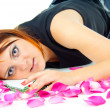 Beautiful girl lying in rose petals — Stock Photo