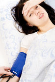 Beautiful girl bad, lying on the bed and measure the pressure — Stock Photo