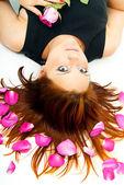 красивая девушка, лежа с лепестками роз — Стоковое фото