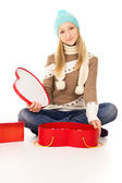 Girl in winter hat sitting with gift boxes — Foto Stock