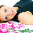 Foto Stock: Beautiful girl lying in rose petals isolated