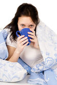 The diseased beautiful girl lying on the bed, and drink medicine — Stock Photo