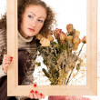 Girl with a frame and a still life of flowers — Stockfoto