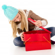 Happy girl sitting on the floor with gifts — Stock Photo