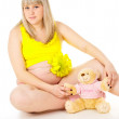 Pregnant girl sits with a toy — Stock Photo