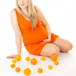 Pregnant woman sitting with oranges — Stock Photo #18773647