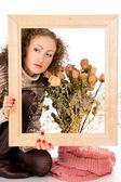 Girl with a frame and a still life of flowers — Stock Photo
