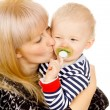 Stock Photo: Mother keep beautiful little baby in her arms, sucking a pacifie