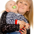 Mother keep merry little baby in her arms, sucking a pacifier — Stock Photo #19649957