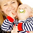 Mother keep nice little baby in her arms, sucking a pacifier — Stock Photo