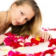 Beautiful blond girl with rose petals — Stockfoto