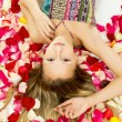 Beautiful girl lying with rose petals — Stock Photo