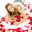 Beautiful girl lying with rose petals — Foto Stock