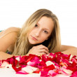 Blonde girl lying with rose petals — Foto Stock