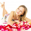 Healthy skin, a beautiful girl lies in petals — Stock Photo