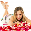 Healthy skin, a beautiful girl lies in rose petals — Stock Photo #23943735