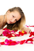 Beautiful blond girl with rose petals — Stock Photo