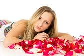 Blond dziewczynka leżąc z płatków róży — Zdjęcie stockowe