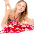 Beautiful girl lies in rose petals — Stock Photo