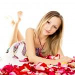 Beautiful girl lies in rose petals — Stock Photo #25007743
