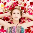 Beautiful girl lies in the petals of roses — Stockfoto