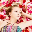 Stock Photo: Beautiful girl lies in the petals of roses