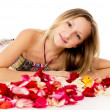 Girl lying in covered by flower petals — Stock Photo #25008609