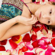 Girl lies in the petals of roses — Stock Photo