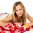 Girl lying in covered by flower petals — Stock Photo #25008631