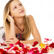 Girl lying in covered by flower petals — Stock Photo #25008633