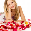 Girl lying in covered by flower petals — Stock Photo #25008649