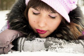 Beautiful girl lying in the snow — Foto de Stock