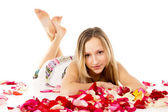 Girl lying in covered by flower petals — Stock Photo