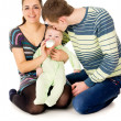 Stock Photo: Happy parents feeds baby