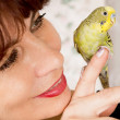In age woman with a parrot — Stock Photo #26270393