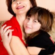Stock Photo: Mother gently hugs its daughter