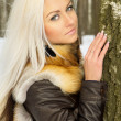 Sexy blond girl in the woods near a tree — Stock Photo