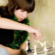 Small the girl was sitting on the sofa at and plays chess — Stock fotografie