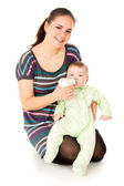 Happy the mother feeds her baby — Stock Photo