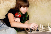 Small the girl was sitting on the sofa at and plays chess — Stock Photo