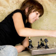 The girl was sitting on the sofa at and plays chess — Foto Stock