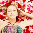Young girl lies in the petals of roses — Stock fotografie