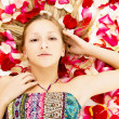 Young girl lies in the petals of roses — Stock Photo #26629497