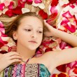 Stock Photo: Girl lies in the petals of roses