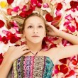 Young girl lies in the petals of roses — Stock Photo