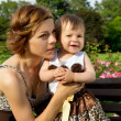 Happy mother with a baby on a bench rest — Stock Photo #31397703