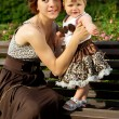 Happy mother with a baby on the bench — Stock Photo