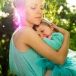 Mom hugs baby at sunset — Stock Photo